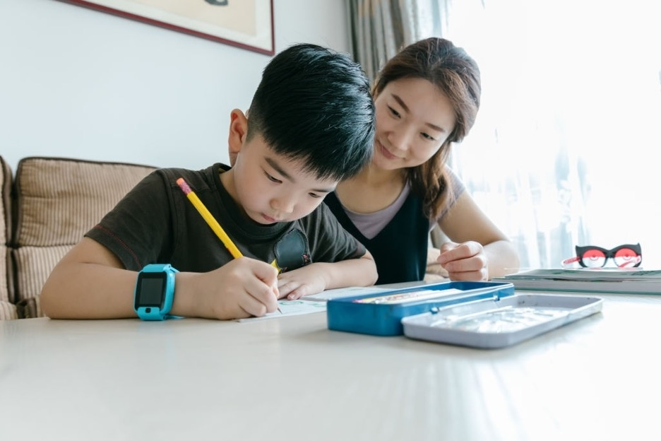 an Asian mum monitoring her son doing homework